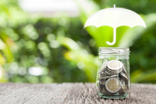 Coverage, insurance or Protection concept, coins in glass , umbrella nature background.